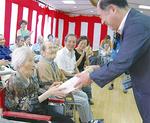 猪瀬さんに記念品を渡す鈴木区長