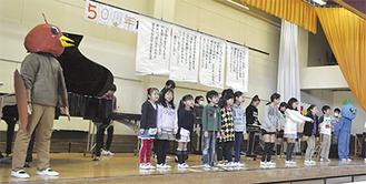 ぴょん(写真左)とユーリンとともに「ハッピー仏向」を歌う児童ら