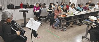 福本さん(写真左)の伴奏で歌う参加者