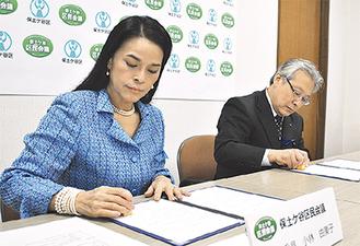 契約書に押印する小林代表(左)と菅井区長