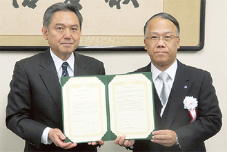 姉妹校提携の合意書を手にする中島校長(写真右)