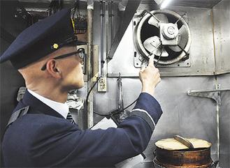 厨房設備を確認する査察員