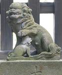 子どもに授乳しながら頭を撫でる母狛犬は「お仕事中」。目線は門前を向き、悪気が入ってこないかにらみを利かせている