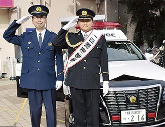 署長と敬礼をする萩原さん(右)