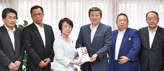募金の目録を林市長に手渡す山谷会長(中央右)