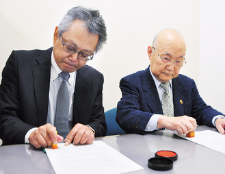 協定書に調印する山崎会長(右)と池田事務局長