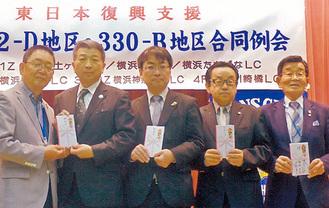 寄付金を手渡す田中会長(写真左)