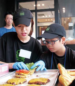 ハンバーガーの作り方を学ぶ小学生