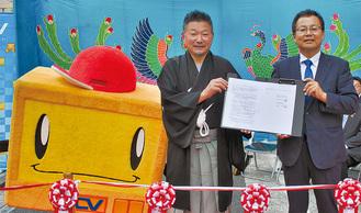 命名権の契約書に調印した安田代表理事(上写真中央)と京代表取締役社長(同右)、写真左は新たな商店街の愛称にも冠されたYCVのマスコットキャラクター「テレミン」
