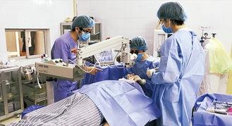 十分な機器が揃うわない中で手術を行う3人