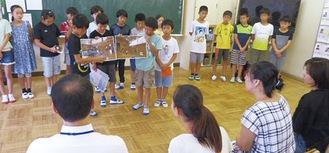 運営資金調達のためプレゼンテーションを行う児童