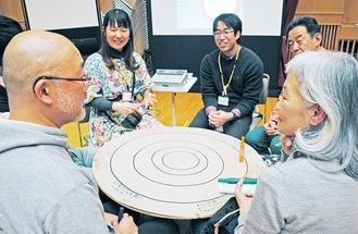 段ボール製の円卓を膝に乗せそれぞれのテーマの課題解決策を話し合う参加者