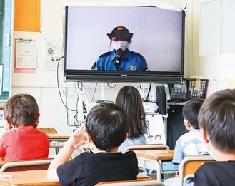 警察官の話に耳を傾ける児童ら