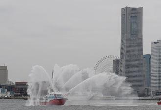 みなとみらいの景色を背に放水を行う消防艇