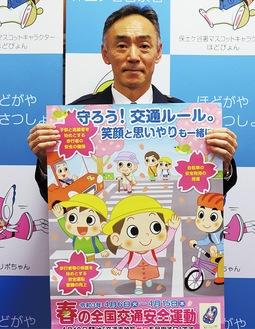 交通安全運動のポスターを持つ新井署長