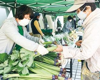 地場野菜を買い求める来場者