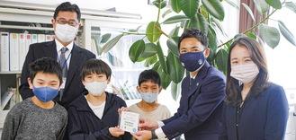 内田さんと仲山さん(右)からDVDが児童代表に手渡された