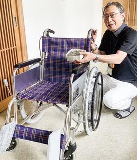 プルタブを手に車椅子を紹介する鈴木会長