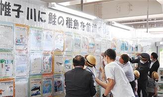 11日に開かれたオープニングセレモニーで関係者と子どもたちが絵を自由通路に掲出した