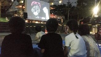 特設されたスクリーンで映画を楽しむ子どもたち