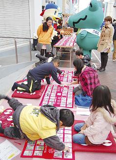 同日開催の「150円商店街」もあり、家族連れが途中参加の場面も。YOUテレビの生中継もあった。