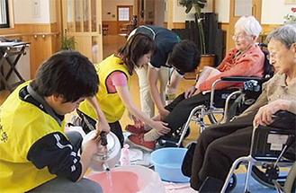 岩手県大槌町で高齢者の足浴を手伝う明学大生