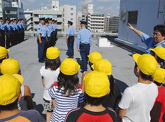 鶴見署屋上で行われた通常点検の様子を見つめる児童
