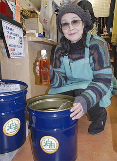 回収した油を手にする佐佐木代表