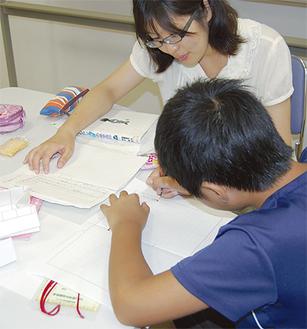 宿題に励む子どもと見守るボランティア