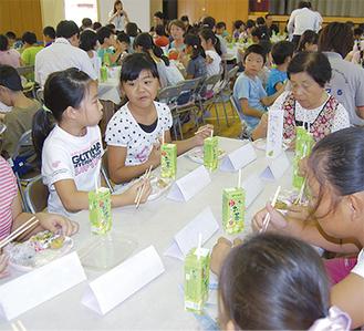 ゴーヤチャンプルーの弁当を食べる児童と地域住民