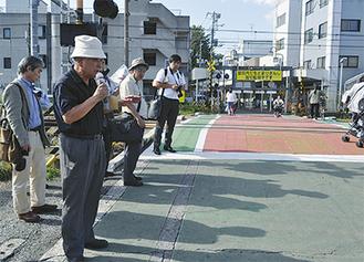 事故現場の踏切で説明する土屋事務局長(左手前)