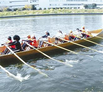 冬晴れの鶴見川を颯爽と進むボート