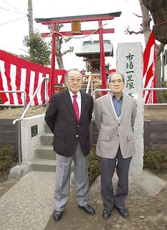 修復工事を終えた一里塚(奥)の前に立つ小林さん(右)と森田会長
