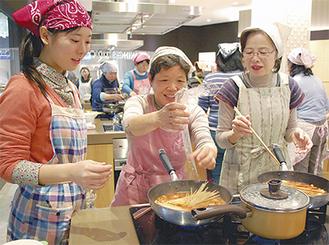 ソースを作るフライパンにパスタを入れる参加者