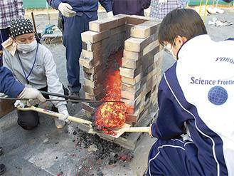 炉からケラを取り出す生徒ら