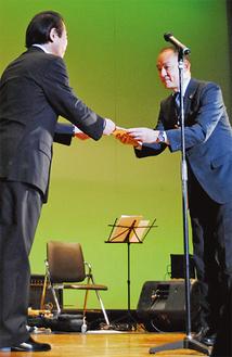 辺見代表(左)から寄付を受け取る伊藤事務局長