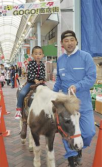 商店街でポニーの乗馬体験をする子ども