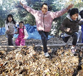 落ち葉のプールに飛び込む子どもたち