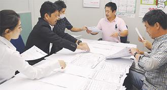 集まった応募用紙を裏返し抽選する実行委員