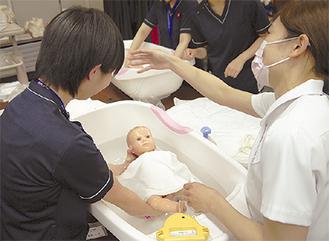 沐浴体験をする生徒(左)
