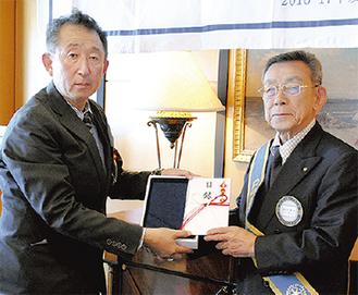松江会長(右)から寄贈を受ける清水校長