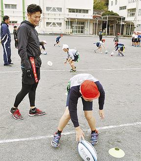 廣瀬さん(左)に見守られボールを転がす練習をする児童
