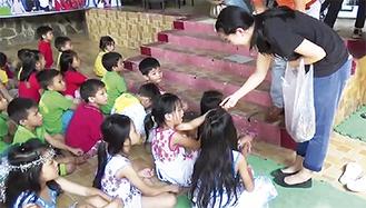 ベトナムの孤児院で文房具を手渡す学生(2015年撮影)