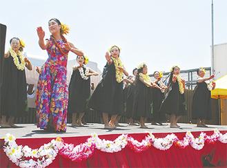 広がる青空の下、手作りの特設ステージで踊る参加者