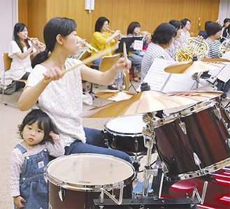 子どもを傍らに練習に励むメンバー