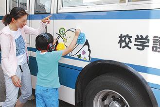 スクールバスにラッピングする児童