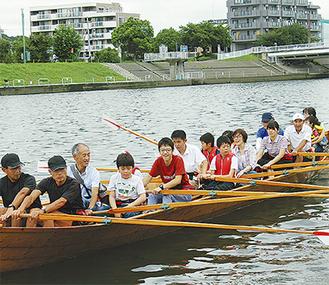 ボートを漕ぐ子どもたちとボランティア