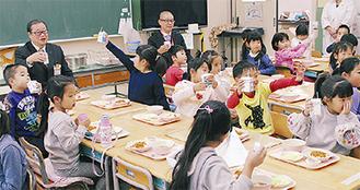 牛乳で乾杯する区長と児童ら