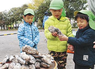 焼き芋を持って喜ぶ園児ら