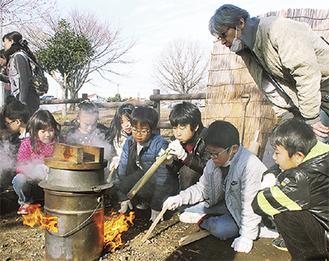 火起こしで水を沸かす児童ら